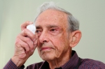 An older male patient demonstrates use of the Whisper eyedrop device.